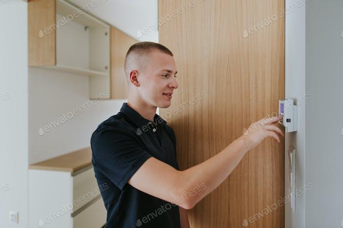Porträt des jungen Mannes Einstellung Thermostat in der neuen Wohnung.