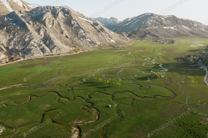 Aerial view of mountain meeting meadow with many paths