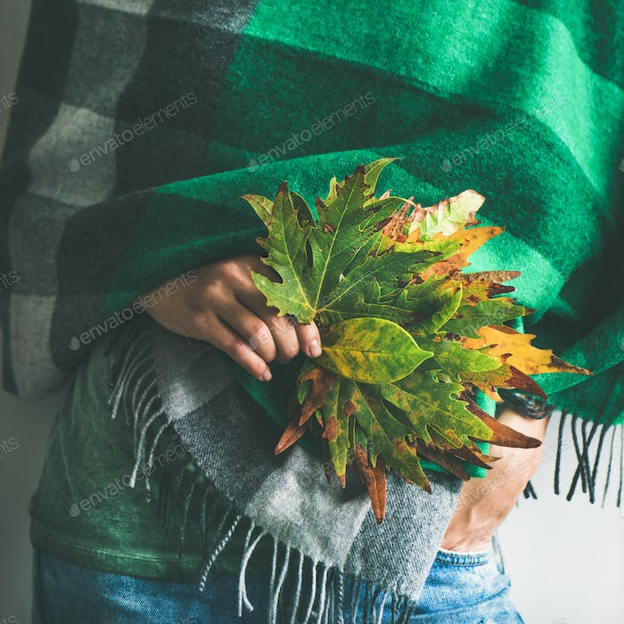 Woman in warm scarf or blanket with leaves, square crop