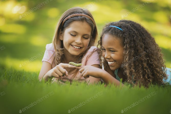 Two girls lying on the grass, one holding a green caterpillar on her finger.