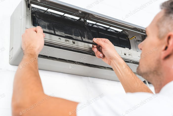 close up view of man fixing filter of air conditioner