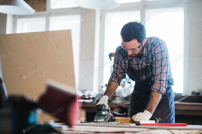 Рабочий измельчает древесину углового шлифовального станка
