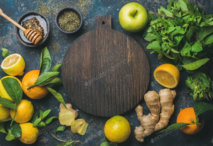 Oranges, mint, lemons, ginger, honey, apple, wooden board in center