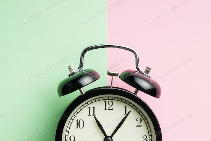 Vintage alarm clock on two tone color background.