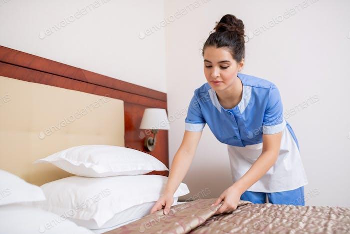 ziemlich junge Brünette Kammer maid in blau uniform machen Bett in hotel Zimmer