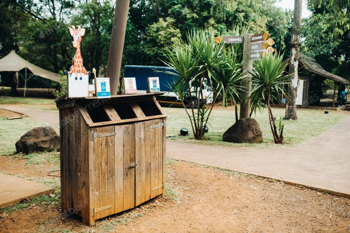 Wooden trash can for collecting separately plastic, cardboard and organic products in a Park on the