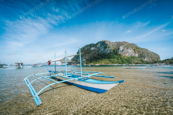 El Nido, Palawan, Philippines. Tourist banca boat on the sandy beach in low tide with huge rock of