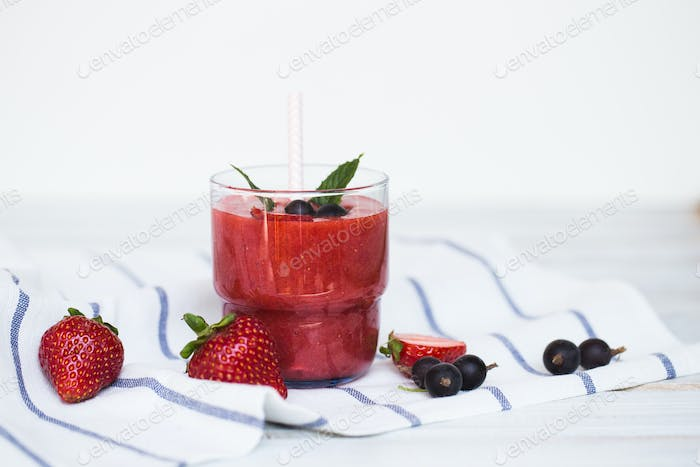 Smoothies of black currant and strawberries with yogurt on a white wooden table.