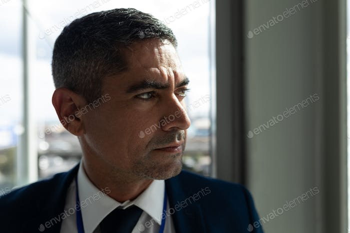 Close-up of businessman face looking away in office against view on outside in background