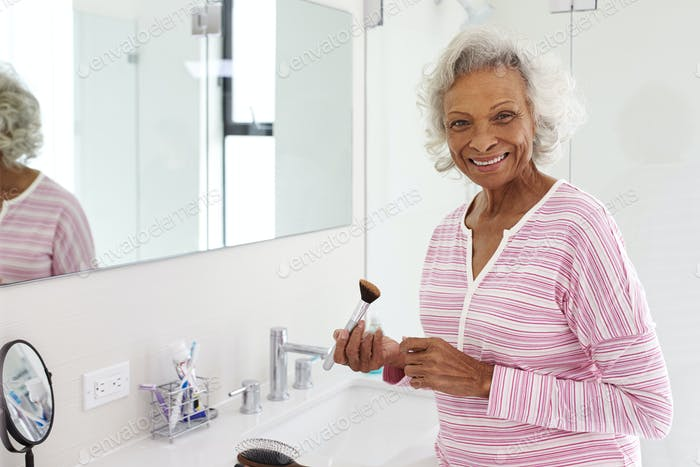 Portrait Of Senior Woman In Bathroom Putting On Make Up