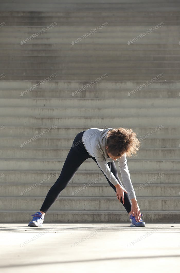 Young woman bending down stretching leg muscles