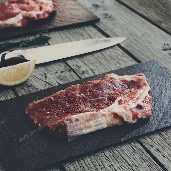 Raw beef steak on dark wooden table background