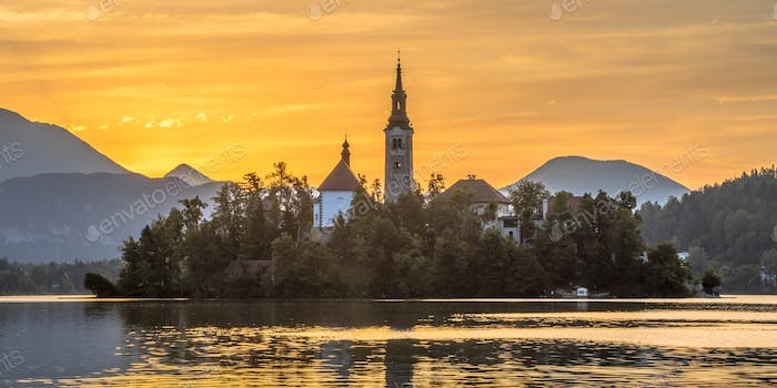 Famous landmark Island in Lake bled with church under orange mor