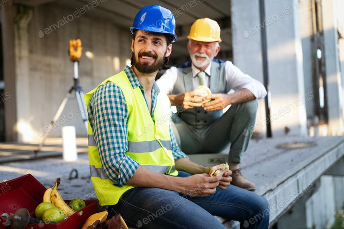 Happy young and senior engineer worker sitting at building site on break