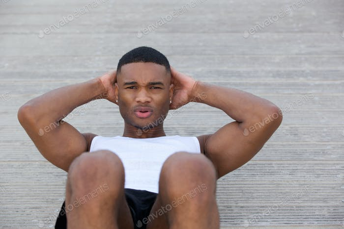 Young man exercising doing sit ups outside