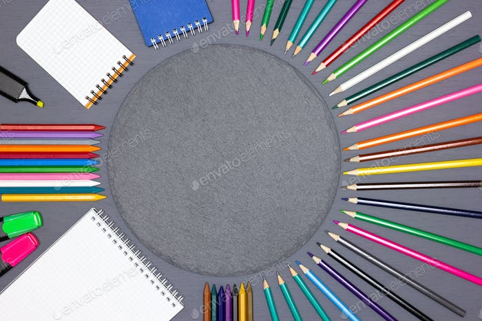 Blank notebooks, felt-tip pens, crayons with round slate chalk board