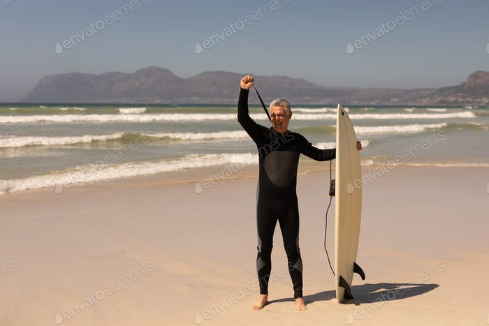 Side vieiw of active senior male surfer standing with surfboard on the beach