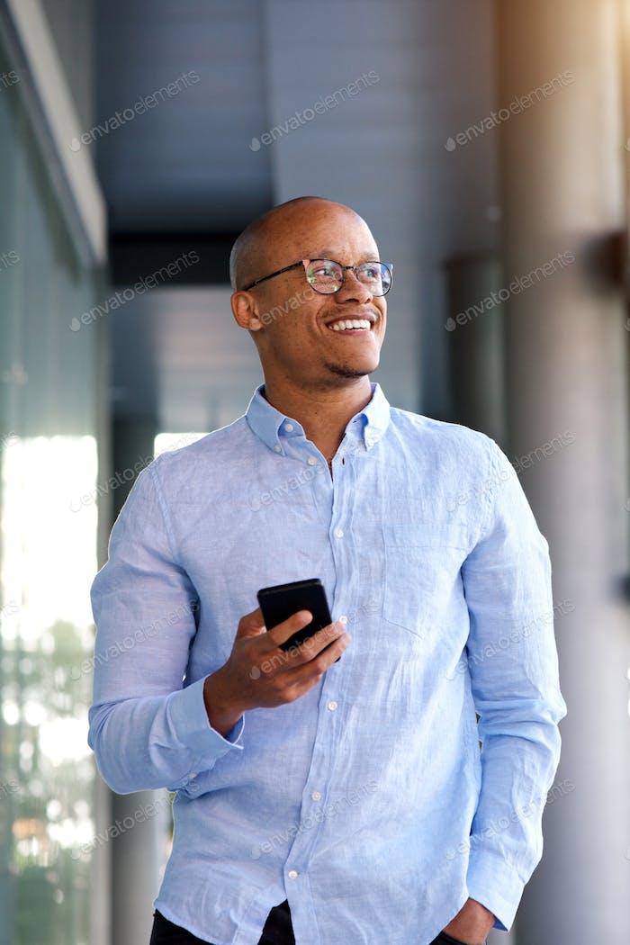 smart aussehende afrikanische Geschäftsmann zu Fuß mit Handy