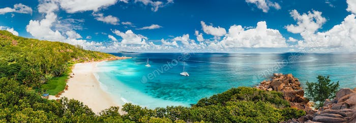 Aerial Pano of Grand Anse beach at La Digue island in Seychelles. White sandy beach with blue ocean