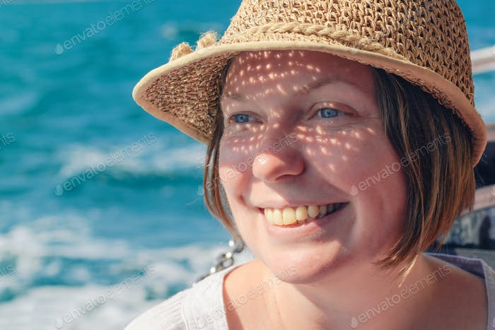 Smiling female tourist with straw hat at seaside