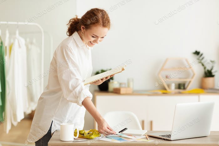 Female fashion stylist holding color samples standing at desk