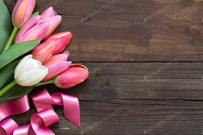 Pink and white tulips on dark wooden background