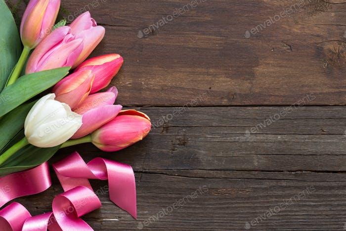 Rosa und weiße Tulpen auf dunklem Holzhintergrund