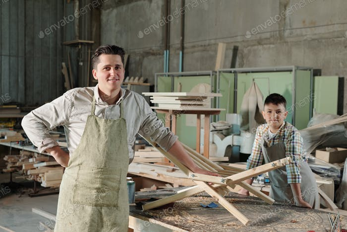 Satisfied furniture makers in workshop