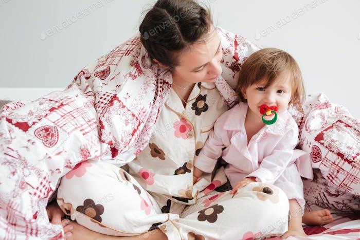 Mutter sitzt im Bett mit ihrer Tochter