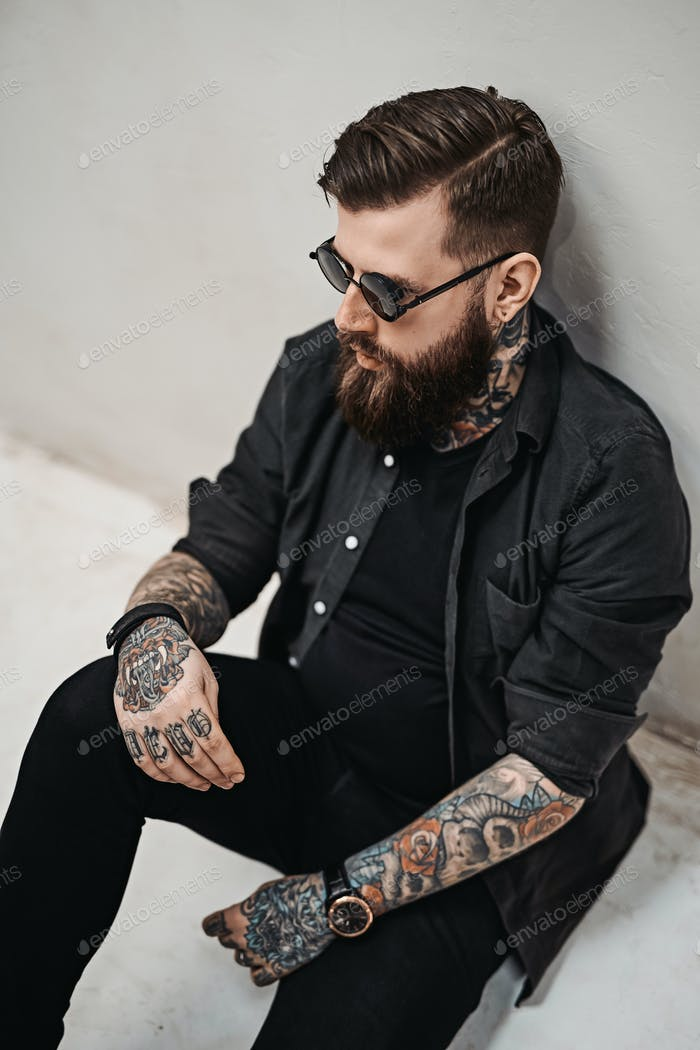 Cool bearded hipster guy in sunglasses sitting of a floor in studio