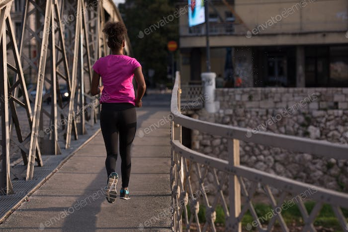 african american woman running across the bridge