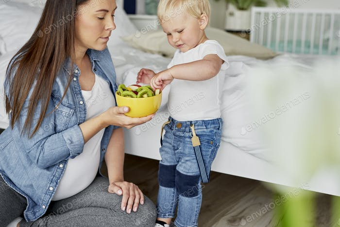 Toddler picking up fruit from the bowl