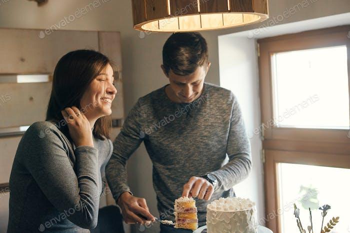 Happy stylish pregnant couple cutting delicious white cream cake