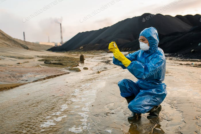 Contemporary female ecologist or researcher making experiments in toxic area