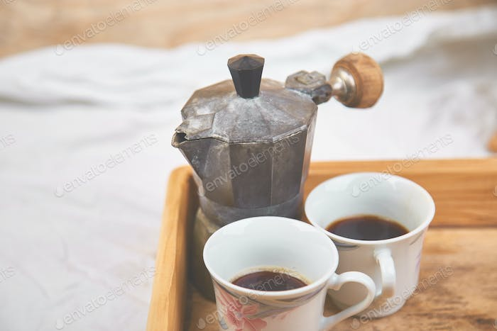 Moka coffee pot with two cup of coffe on wooden tray