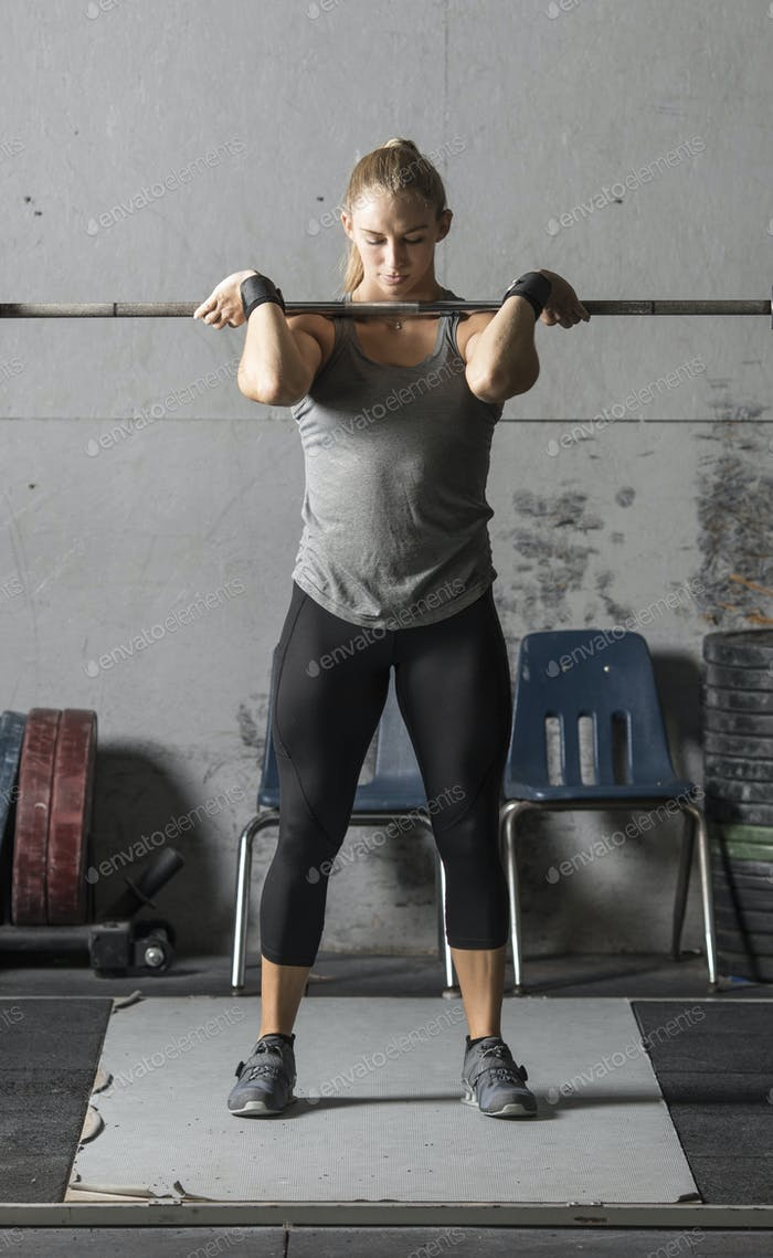 Strong young female weight lifter training in grungy gym.