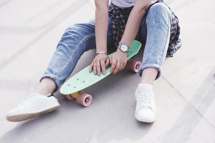 Beautiful teen female skater sitting on ramp at the skate park. Concept of summer urban activities