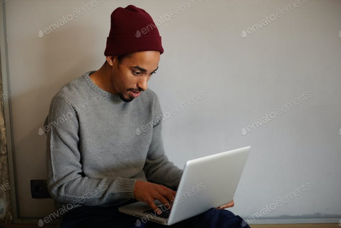 Shot of attractive young bearded dark skinned male in grey sweater and burgundy