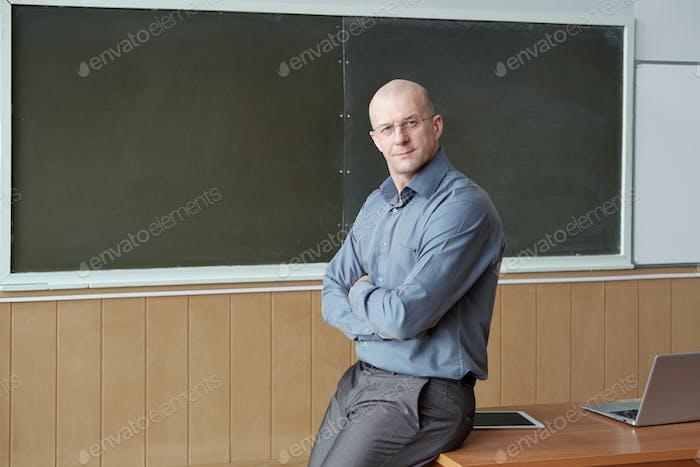 Bald professor of university in smart casualwear sitting on desk against blackboard