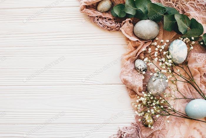 Stilvolle Ostereier mit Frühlingsblumen auf rustikalem Stoff