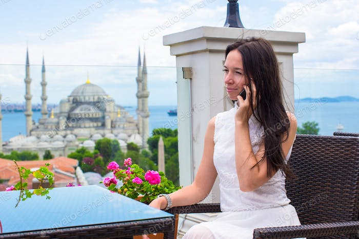 Young woman on terrace with stunning view of the city