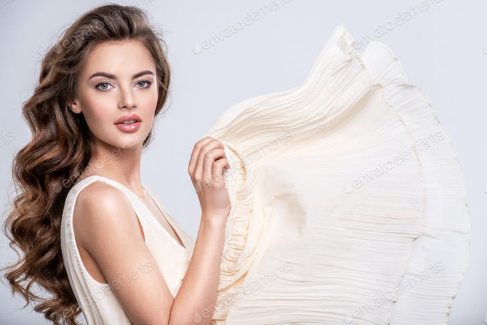 Portrait of a beautiful woman with a long hair in a beige dress.