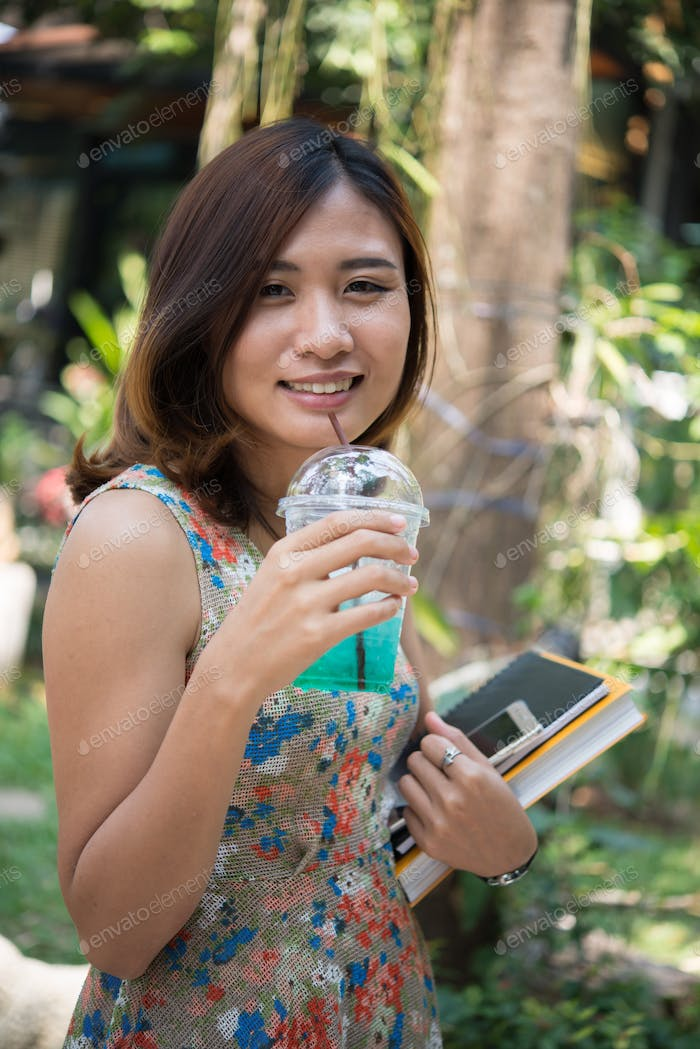 Happy beautiful student girl holding folders and books walking drinking iced drink outdoors.