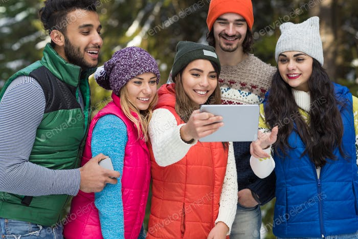 People Group Using Tablet Computer Snow Forest Happy Smiling Young Friends Walking Outdoor Winter