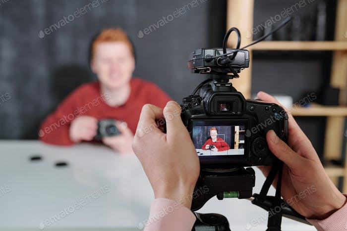 Operator holding camera in front of male blogger showing new photo equipment