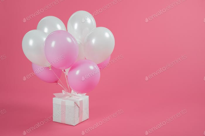 Gift box and balloons on pink background