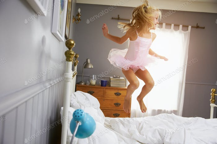Girl In Ballerina Outfit Jumping On Parents Bed
