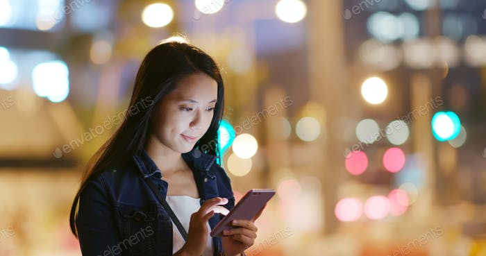 Young Woman use of mobile phone in city at night