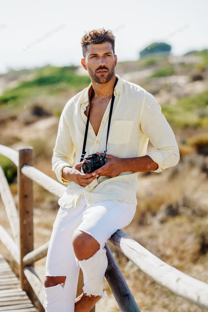 Handsome man photographing in a coastal area