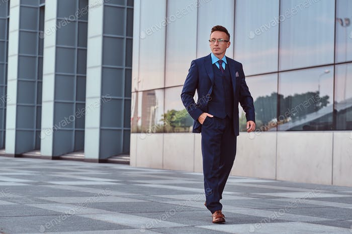 Уверенный бизнесмен, одетый в элегантный костюм, стоящий на открытом воздухе на фоне городского пейзажа.